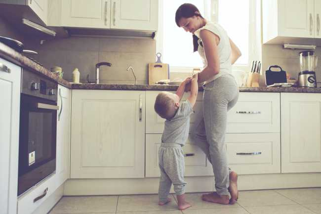 Mom with her 2 years old child cooking holiday pie in the kitche