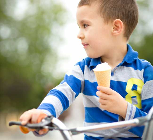 Little boy is eating ice-cream while sitting on bike, outdoor sh