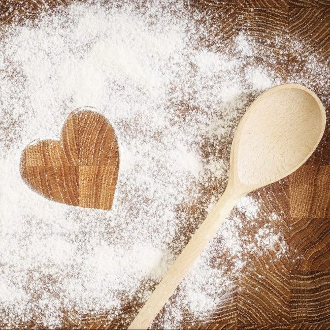 Heart of white flour on a wooden board. Cooking with love. Holid